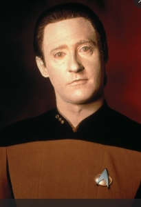 Bust of android Data in uniform, head tilted down to his right, looking at camera. Skin has yellow tint.